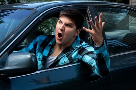 7927601 - an irritated young man driving a vehicle is expressing his road rage.