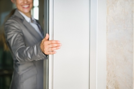 15652651 - closeup on business woman hand holding elevator door