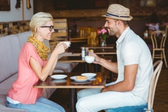 42515193 - cute couple on a date talking over a cup of coffee at the cafe